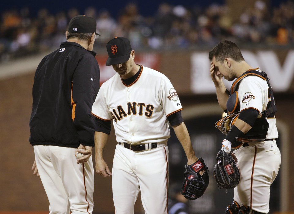 Photo - San Francisco Giants starting pitcher Tim Hudson, center, walks to the dugout after being taken out of the baseball game by manager Bruce Bochy, left, as catcher Buster Posey, right, waits during the sixth inning Tuesday, June 24, 2014, in San Francisco. (AP Photo/Eric Risberg)