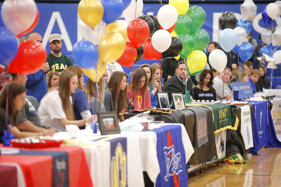 Photo - Deer Creek athletes sit a tables during a signing day ceremony at Deer Creek High School, Wednesday, Feb. 7, 2018.  Photo by Bryan Terry, The Oklahoman