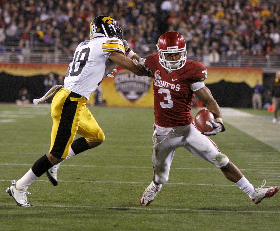 Oklahoma's Brennan Clay (3) fights off Iowa's Micah Hyde (18) during the Insight Bowl college football game between the University of Oklahoma (OU) Sooners and the Iowa Hawkeyes at Sun Devil Stadium in Tempe, Ariz., Friday, Dec. 30, 2011. Photo by Bryan Terry, The Oklahoman