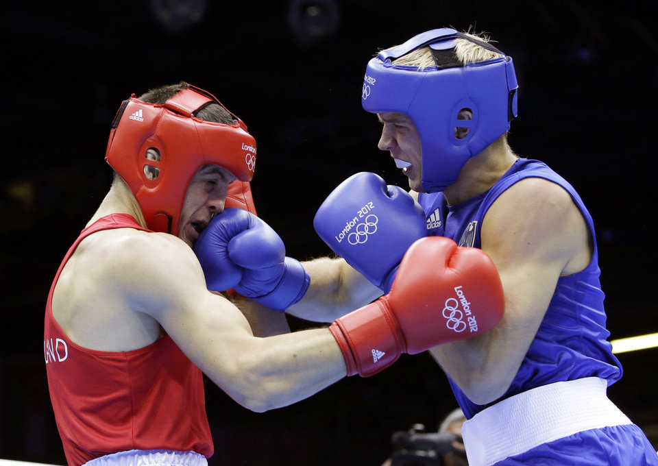 Photo - Ireland's Darren O'Neill, left, fights Germany's Stefan Hartel during their men's middle weight 75-kilogram boxing match at the 2012 Summer Olympics in London. AP Photo  Andrew Medichini