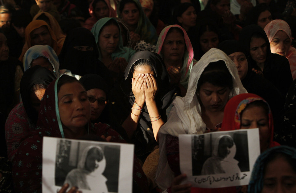 Photo -   A supporter of Pakistani political party Muttahida Qaumi Movement (MQM), center, reacts while she and other women chant prayers in support of 14-year-old schoolgirl Malala Yousufzai, who was shot on Tuesday by the Taliban for speaking out in support of education for women, at the (MQM)' headquarter in Karachi, Pakistan, Wednesday, Oct. 10, 2012. Pakistani doctors successfully removed a bullet Wednesday from the neck of a 14-year-old girl who was shot by the Taliban for speaking out in support of education for women, a government minister said. Writing on poster read,