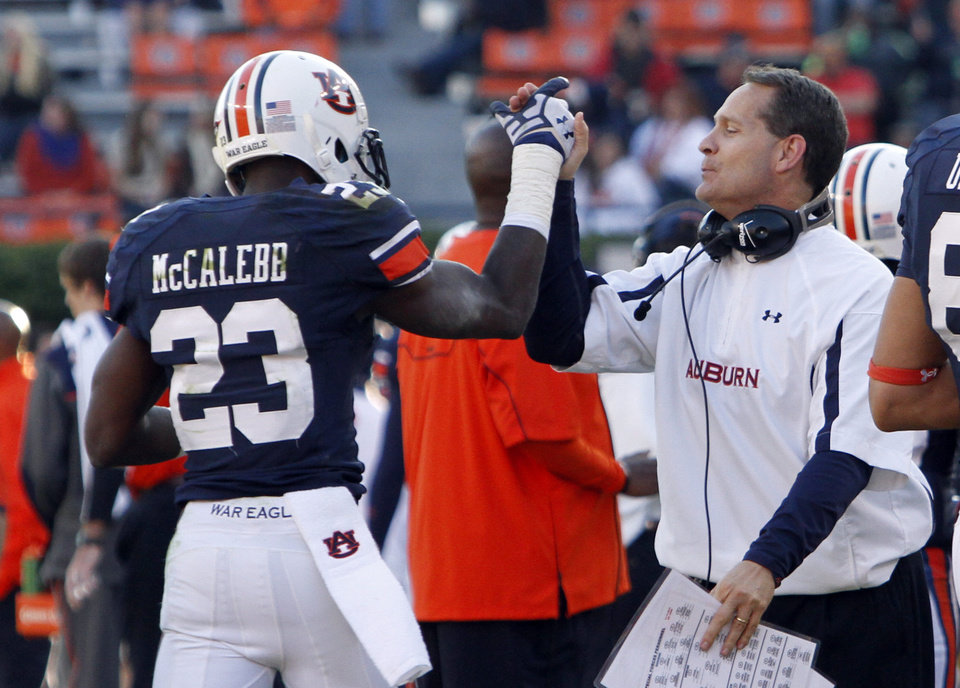 Photo -   Auburn coach Gene Chizik, right, gives Auburn running back Onterio McCalebb (23) a high-five after he scored a touchdown during the second half of an NCAA college football game against Alabama A&M on Saturday, Nov. 17, 2012 in Auburn, Ala. Auburn defeated Alabama A&M 51-7. (AP Photo/Butch Dill)