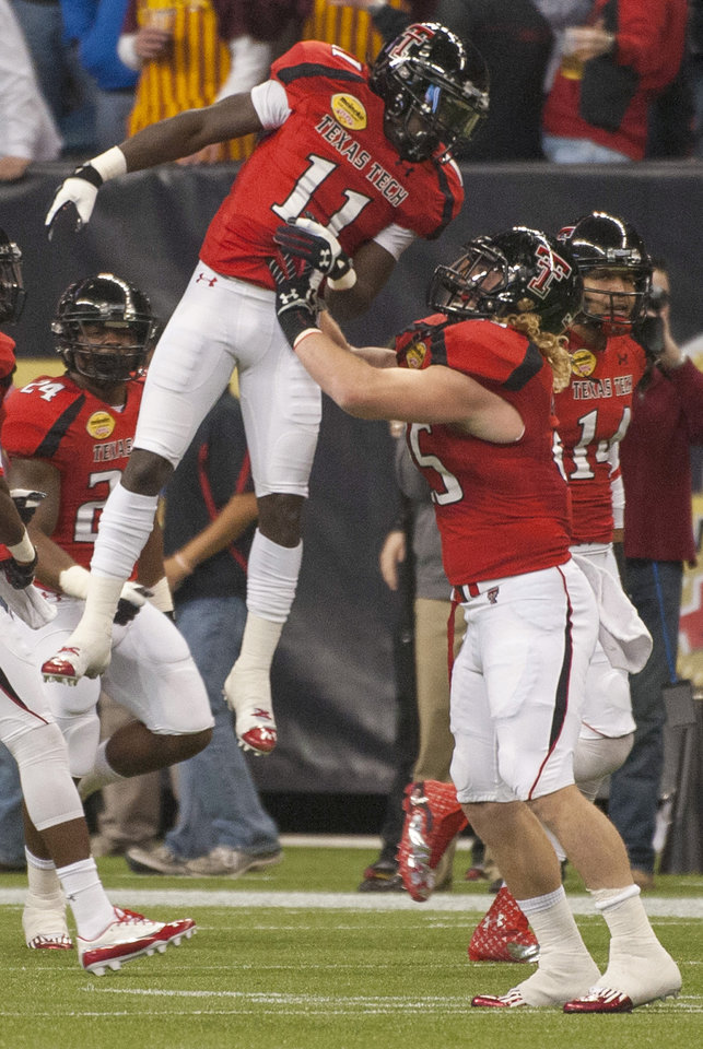 Texas Tech's Jakeem Grant (11) celebrates with Blake Dees, right, after returning a kickoff for a touchdown against Minnesota during the first quarter of the Meineke Car Care Bowl NCAA college football game, Friday, Dec. 28, 2012, in Houston. (AP Photo/Dave Einsel)