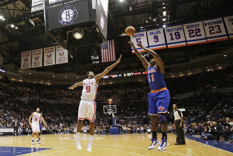 Photo - New York Knicks' Ronnie Brewer (11) shoots over Brooklyn Nets' MarShon Brooks (9) during the first half of a preseason NBA basketball game at Nassau Coliseum, Wednesday, Oct. 24, 2012, in Uniondale, N.Y. (AP Photo/Frank Franklin II)