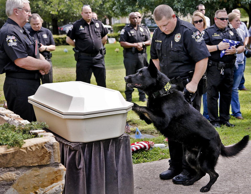 Oklahoma County Sheriff\'s Deputy Sean Steadman and his K-9 partner Bose offer final farewells during funeral services for K-9 Deputy Eron at Precious Pets Cemetery on Thursday, July 25, 2013 in Spencer, Okla. Deputy Eron started with the Oklahoma County Sheriff\'s office in 2004, serving eight years as a Bomb Detection K-9 before his retirement. Eron\'s last call of service for his career was tracking and capturing a suspect for the Choctaw Police Dept. Photo by Chris Landsberger, The Oklahoman