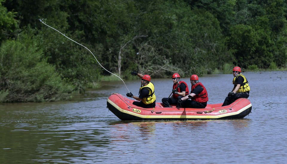 Photo - Members of a the Shertz Fire Department search Sunday, May 26, 2013, in Shertz, Texas, for a missing teen who was swept away in a rain swollen Cibilo Creek Saturday. (AP Photo/Eric Gay)