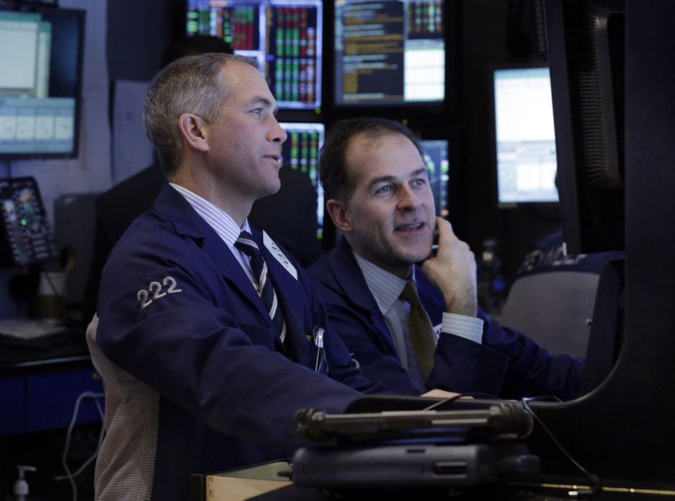 Photo - Traders work in their booth on the floor of the New York Stock Exchange Tuesday, Jan. 28, 2014. Stocks are higher in early trading on Wall Street as the stock market turns positive after three days of losses. (AP Photo/Richard Drew)