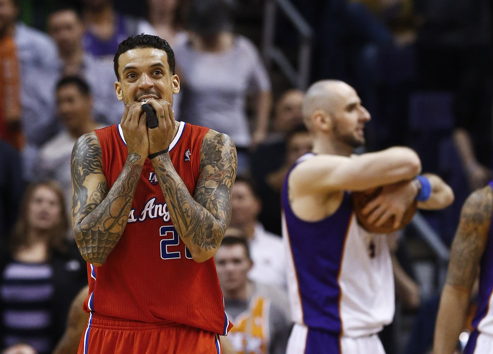 Photo - Los Angeles Clippers' Matt Barnes, left, reacts to a foul being called on the Clippers as Phoenix Suns' Marcin Gortat, of Poland, grabs the ball during the second half in an NBA basketball game Thursday, Jan. 24, 2013, in Phoenix.  The Suns defeated the Clippers 93-88.(AP Photo/Ross D. Franklin)
