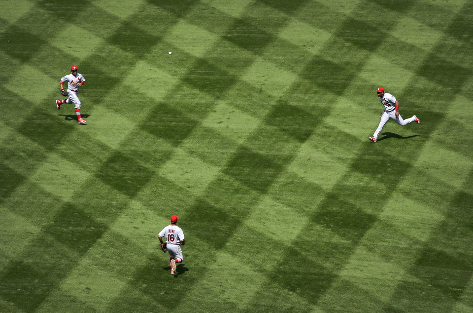 Photo - St. Louis Cardinals center fielder Jon Jay, clockwise from top left, right fielder Oscar Taveras and second baseman Kolten Wong chase after a fly ball by Baltimore Orioles' Nick Markakis in the third inning of an interleague baseball game, Sunday, Aug. 10, 2014, in Baltimore. (AP Photo/Patrick Semansky)