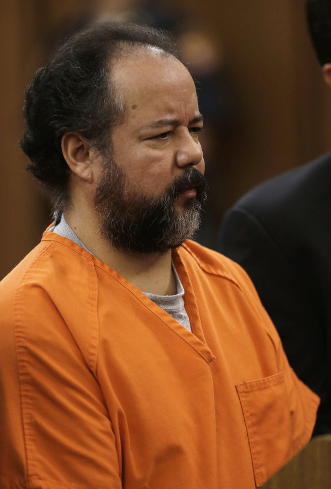 Photo - Ariel Castro stands before a judge during his arraignment on an expanded 977-count indictment Wednesday, July 17, 2013, in Cleveland. Castro is charged with kidnapping and raping three women over a decade in his Cleveland home. Castro pleaded not guilty to 512 counts of kidnapping and 446 counts of rape. (AP Photo/Tony Dejak)