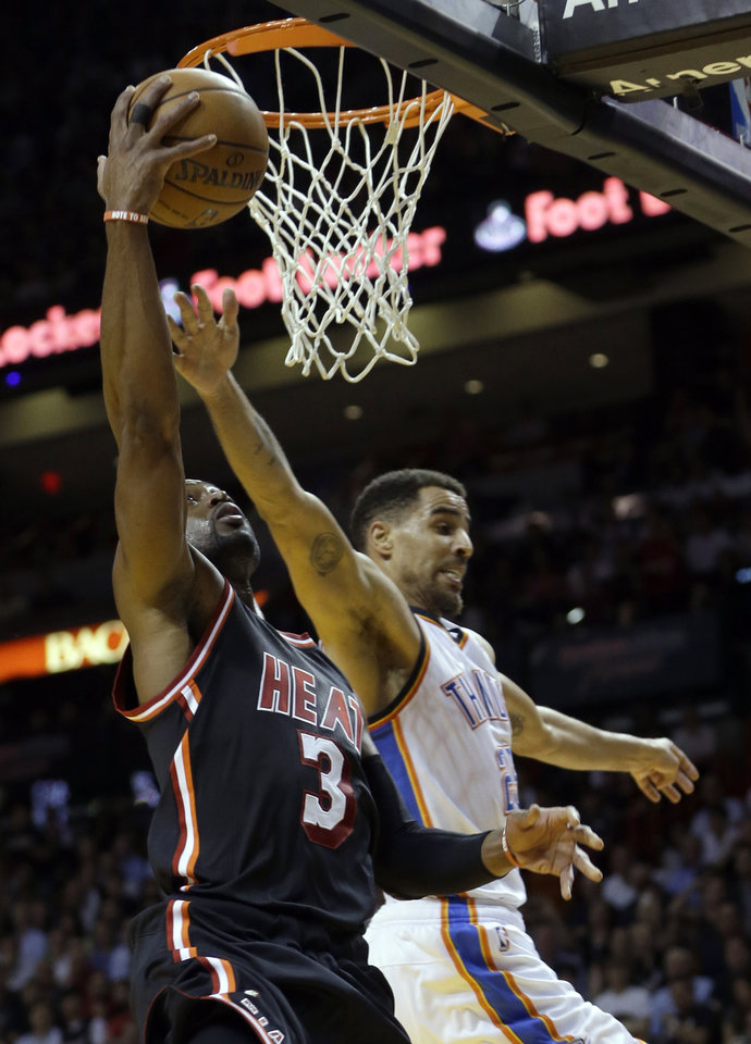 Photo - Miami Heat guard Dwyane Wade (3) goes up to the basket against Oklahoma City Thunder guard Thabo Sefolosha (25) during the second period of an NBA basketball game in Miami, Wednesday, Jan. 29, 2014. The Thunder won 112-95. (AP PhotoAlan Diaz)