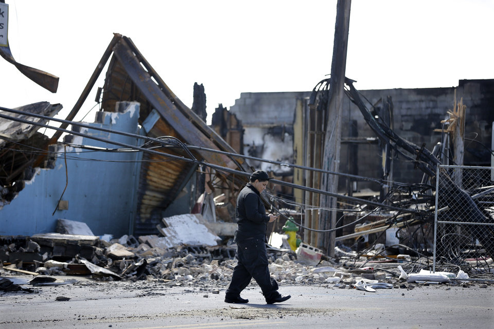 Photo - A man walks past charred rubble in Seaside Heights, N.J., Tuesday, Sept. 17, 2013, after a fire last Thursday that started near a frozen custard stand in Seaside Park,  quickly spread north into neighboring Seaside Heights. More than 50 businesses in the two towns were destroyed. The massive boardwalk fire in New Jersey began accidentally, the result of an electrical problem, an official briefed on the investigation said Tuesday. (AP Photo/Mel Evans)