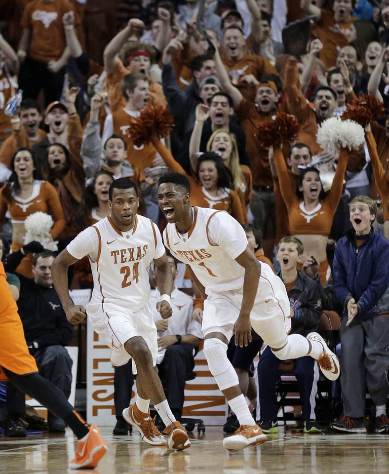 Photo - Texas' Martez Walker (24) and Isaiah Taylor (1) celebrate a score by Walker against Oklahoma State during the second half on an NCAA college basketball game, Tuesday, Feb. 11, 2014, in Austin, Texas. Texas won 87-68. (AP Photo/Eric Gay)