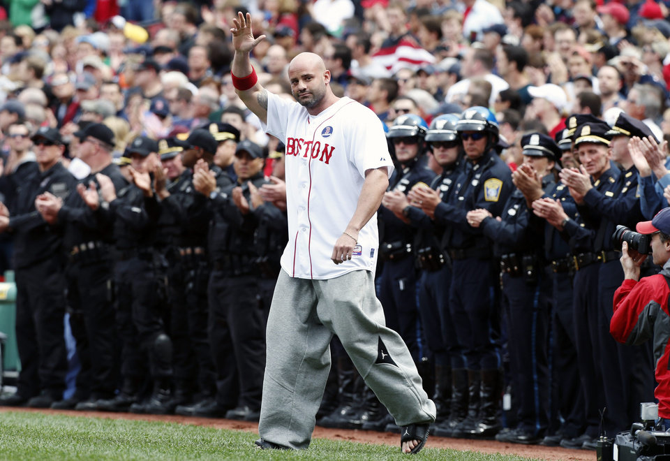 Boston Marathon bombing victim Steven Byrne waves as he comes onto the field for a ceremonial first pitch before a baseball game between the Boston Red Sox and the Kansas City Royals in Boston, Saturday, April 20, 2013. (AP Photo/Michael Dwyer) ORG XMIT: MAMD136