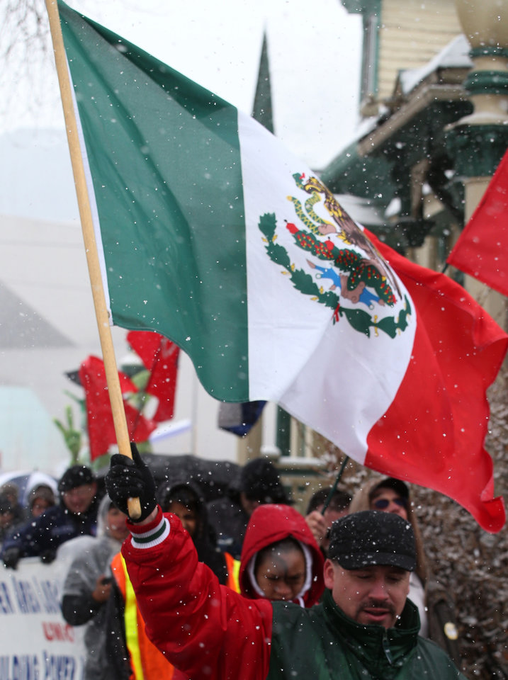 A marcher carries a Mexico flag as protesters brave the cold and snow as they march from the Capitol to a park in Denver on Wednesday, May 1, 2013. About 200 people gathered at the Capitol for immigration reform. The May Day rallies carry a special sense of urgency this year, two weeks after a bipartisan group of senators introduced a bill that would bring many of the estimated 11 million living in the U.S. illegally out of the shadows. Colorado's rally comes just after the governor signed a bill allowing students in the country illegally to pay in-state tuition at state colleges and universities, ending a 10-year political battle.(AP Photo/Ed Andrieski)