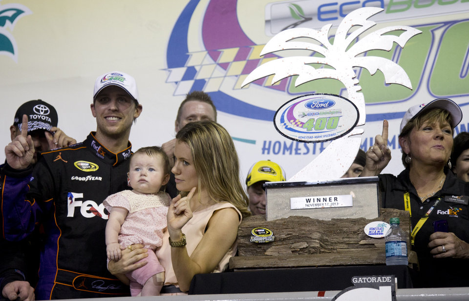 Photo - Denny Hamlin,, front left, his wife, Jordan, and daughter, Taylor, celebrate after he won the NASCAR Sprint Cub Series auto race in Homestead, Fla., Sunday, Nov. 17, 2013. (AP Photo/J Pat Carter)