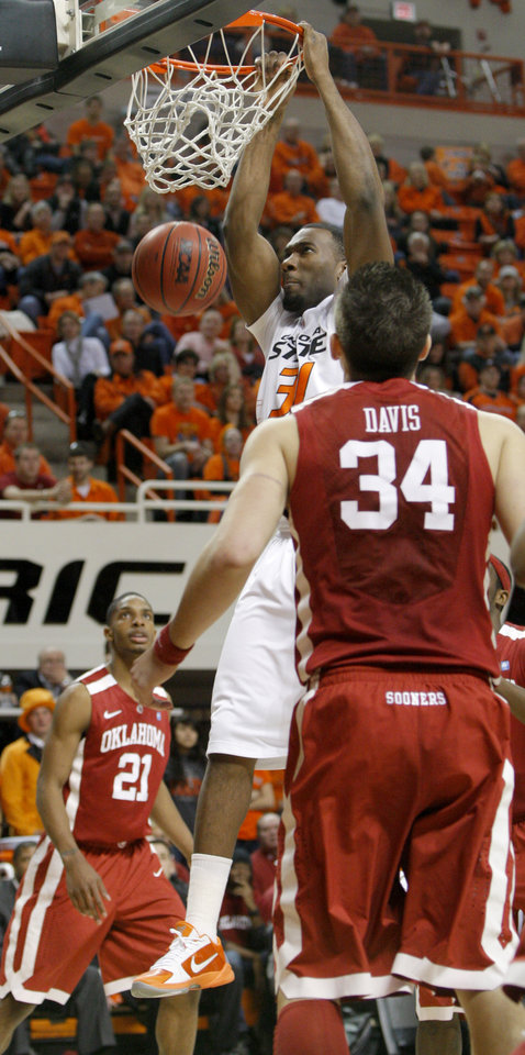 Photo - Oklahoma State's Matt Pilgrim (31) dunks the ball as Oklahoma's Cameron Clark (21) and Cade Davis (34) watch during the Bedlam men's college basketball game between the University of Oklahoma Sooners and Oklahoma State University Cowboys at Gallagher-Iba Arena in Stillwater, Okla., Saturday, February, 5, 2011. Photo by Bryan Terry, The Oklahoman