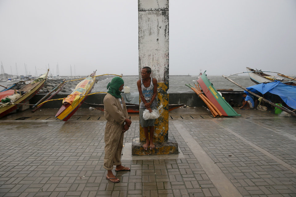 Photo - Men stand as small fishing boats are laced by the seawall amid strong winds and slight rain brought by Typhoon Koppu Sunday, Oct. 18, 2015 in Manila, Philippines. The slow-moving typhoon blew ashore with fierce wind in the northeastern Philippines early Sunday, toppling trees and knocking out power and communications. Officials said there were no immediate reports of casualties. (AP Photo/Bullit Marquez)
