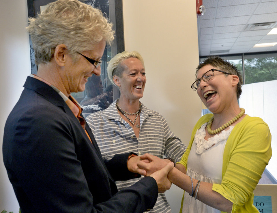 Photo - Julie Hoehing, left, and Nancy Cooley, right, laugh after friend Dana Derichsweiler, middle, performed a marriage ceremony at the Boulder County Clerk and Recorder'ss Office in Boulder, Colo., Tuesday, July 1, 2014. Although Colorado's constitution bans same-sex marriage, a ruling from the 10th U.S. Circuit Court of Appeals in Denver last week regarding a Utah case said states cannot prevent people from marrying based on their gender. That motivated Boulder County Clerk Hillary Hall to begin issuing marriage licenses, even though the 10th Circuit put its ruling on hold pending an appeal. (AP Photo/The Daily Camera, Mark Leffingwell)