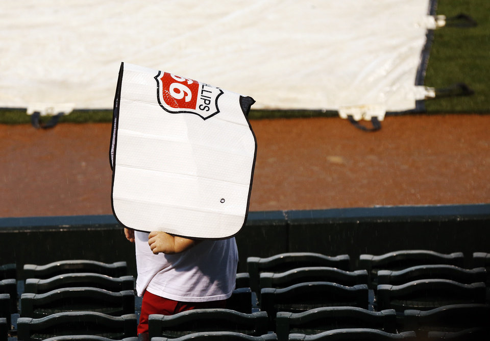 Photo - A fan walks through the stands during a rain delay before the Bedlam college baseball game between Oklahoma and Oklahoma State in the Big 12 baseball tournament at the Chickasaw Bricktown Ballpark in Oklahoma City,  Friday, May 23, 2014. Photo by Nate Billings, The Oklahoman