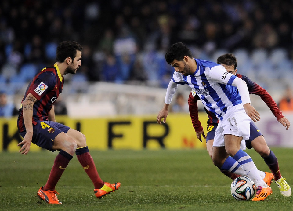 Photo - Real Sociedad's Carlos Vela of Mexico, right, tries to control the ball in front FC Barcerlona's Francesc Fabregas, during their Spanish Copa del Rey semifinal second leg soccer match, at Anoeta stadium, in San Sebastian northern Spain, Wednesday, Feb. 12, 2014. (AP Photo/Alvaro Barrientos)