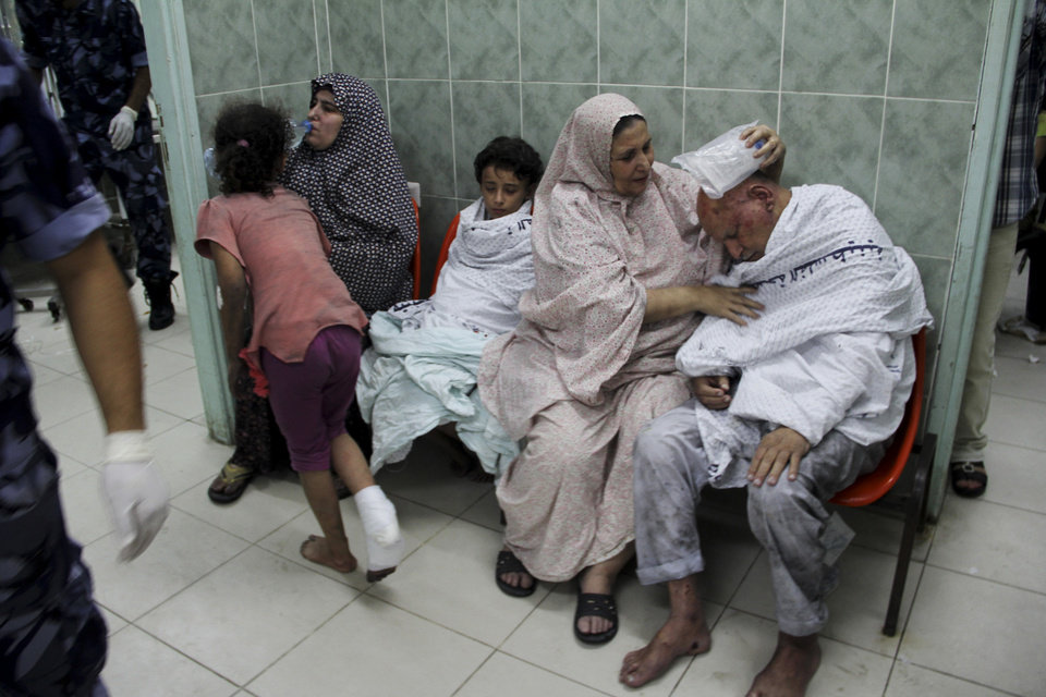 Photo - Palestinians wait for treatment, following an Israeli airstrike on a building, at the treatment room of al Najar hospital in Rafah in the southern Gaza Strip, Thursday, Aug. 21, 2014. (AP Photo/Hatem Ali)