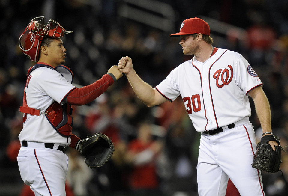 Photo - Washington Nationals relief pitcher Aaron Barrett (30) celebrates 5-0 win over the Miami Marlins with catcher Jose Lobaton, left, during the inning of a baseball game, Tuesday, April 8, 2014, in Washington. (AP Photo/Nick Wass)