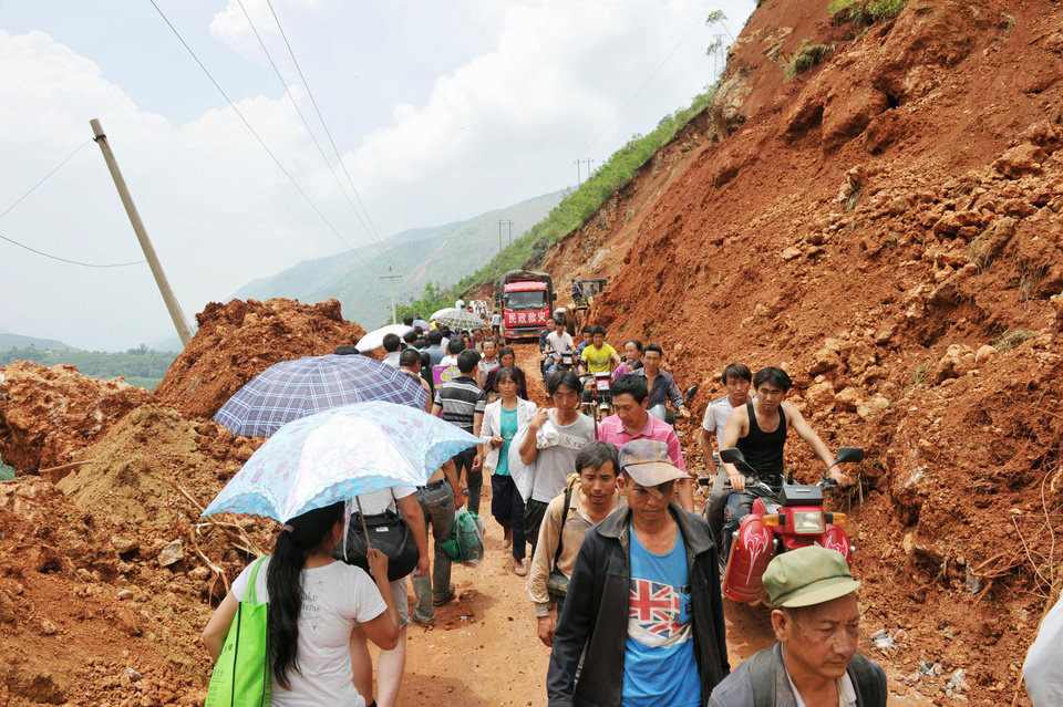 Photo - People walk through a mountain path narrowed by Sunday's earthquake in Ludian County of Zhaotong City in southwest China's Yunnan Province, Monday, Aug. 4, 2014. Rescuers dug through shattered homes Monday looking for survivors of a strong earthquake in southern China's Yunnan province that killed hundreds and injured more than a thousand people. (AP Photo/Kyodo News) JAPAN OUT