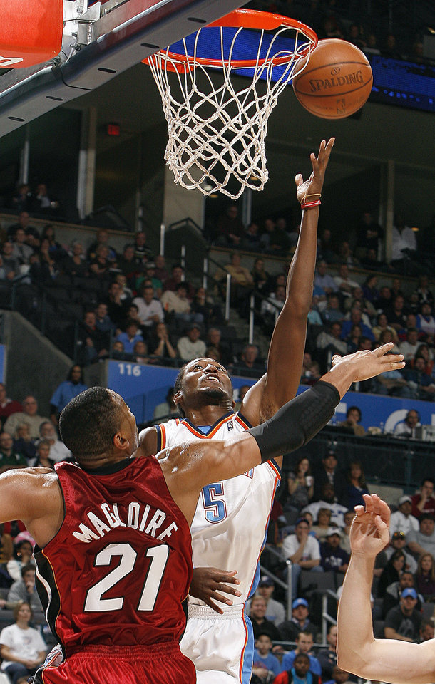 Photo - Oklahoma City's Kyle Weaver (5) shoots over Miami's Jamaal Magloire (21) during the NBA game between the Oklahoma City Thunder and the Miami Heat Sunday Jan. 18, 2009, at the Ford Center in Oklahoma City. PHOTO BY SARAH PHIPPS, THE OKLAHOMAN