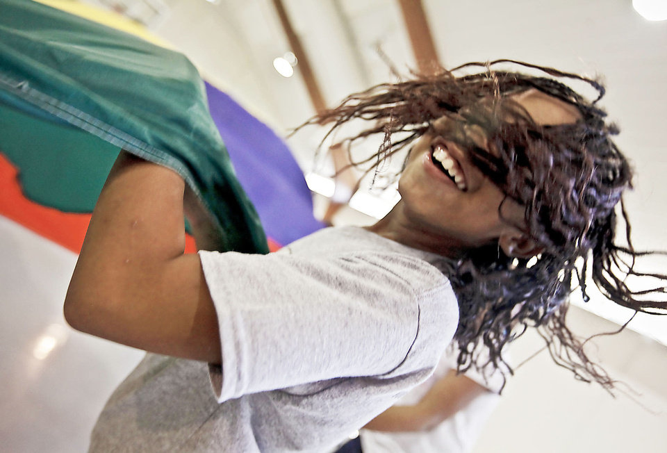 Photo - Right: Jaytoria Minnis waves the parachute during the Kids Rock Camp.