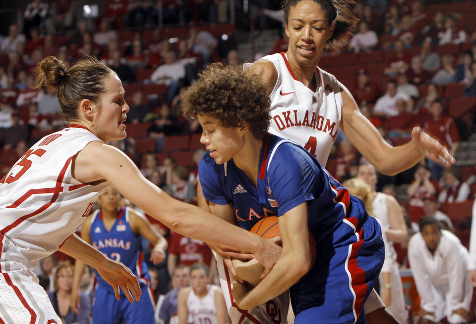 Oklahoma's Whitney Hand (25) and Nicole Griffin (4) fight Monica Engelman (13) for control of the ball during the women's college basketball game between the Oklahoma Sooners and the Kansas Jayhawks at the LLoyd Noble Center in Norman, Okla., Sunday, March, 4, 2011. Photo by Sarah Phipps, The Oklahoman