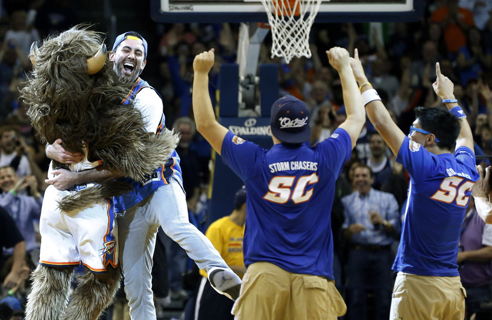 Photo - FILE - In this Monday, Nov. 18, 2013, file photo, Cameron Rodriguez, second from left, celebrates with Oklahoma City Thunder mascot Rumble, left, after hitting a half-court shot to win $20,000 during a timeout of an NBA basketball game between the Thunder and the Denver Nuggets in Oklahoma City. Rodriguez may not be able to keep both the money and his eligibility to compete in college athletics. (AP Photo/Sue Ogrocki, File)