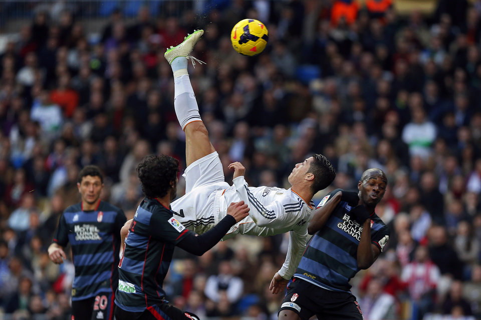 Photo - 10ThingstoSeeSports - Real Madrid's Cristiano Ronaldo, of Portugal, top, tries to score in between opposition players during a Spanish La Liga soccer match between Real Madrid and Granada at the Santiago Bernabeu stadium in Madrid, Spain, Saturday, Jan. 25, 2014. (AP Photo/Andres Kudacki, File)