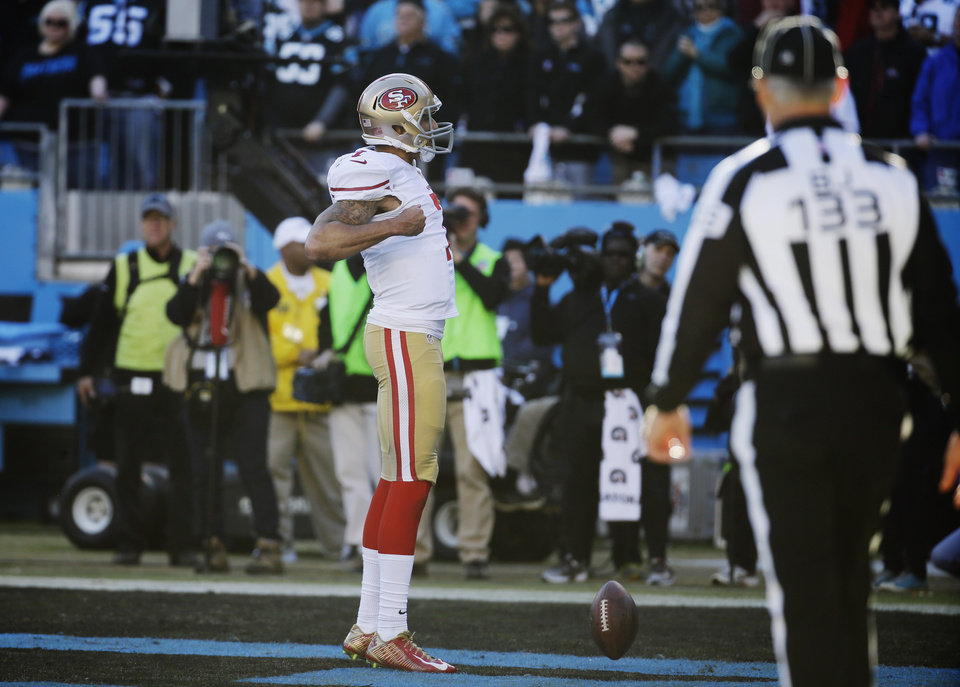 Photo - San Francisco 49ers quarterback Colin Kaepernick (7) celebrates after scoring a touchdown against the Carolina Panthers during the second half of a divisional playoff NFL football game, Sunday, Jan. 12, 2014, in Charlotte, N.C. (AP Photo/John Bazemore)