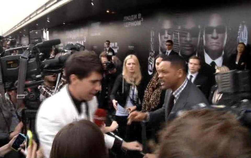 Photo -   In this video image taken from AP video U.S. actor Will Smith, center right, reacts after he was embraced by reporter Vitalii Sediuk, white suit, from the Ukrainian television channel 1+1 on the red carpet before the premiere of