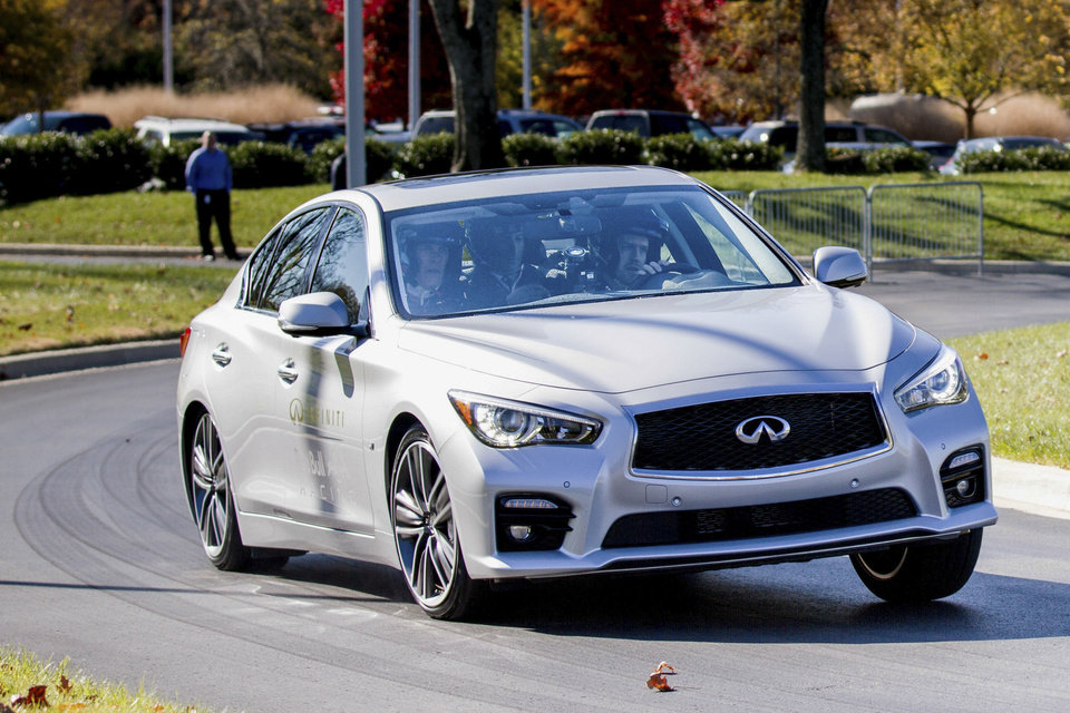 Photo - Formula One driver Sebastian Vettel gives test rides in a new Infiniti Q50 to employees at Nissan Motor Co.'s North American headquarters in Franklin, Tenn., on Wednesday, Nov. 13, 2013. (AP Photo/Erik Schelzig)