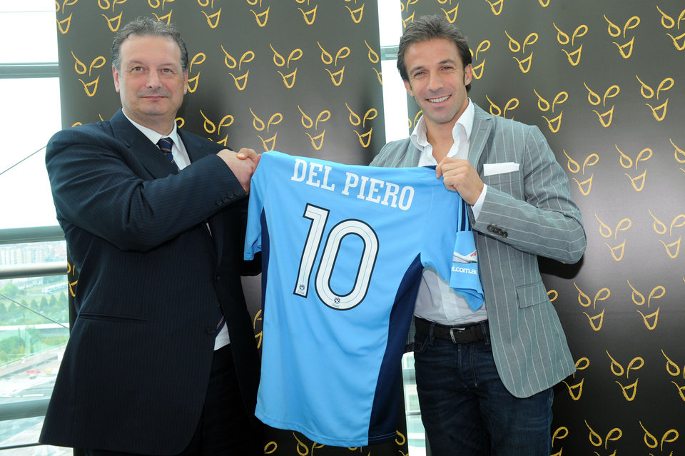 Photo -   Former Italy and Juventus forward Alessandro Del Piero, right. poses with Sydney FC shirt next to club Ceo Tony Pignatta at the Lingotto Palace in Turin, Italy,Wednesday, Sept. 5, 2012. Del Piero is joining Sydney FC in a deal that will make him the highest-profile player in the A-League. The two-year deal is reportedly worth $2 million per season, which will make Del Piero the highest paid athlete in Australia's four football codes, including rugby league, rugby union and Australian Rules. The 37-year-old Del Piero reportedly turned down offers from English Premier League clubs Liverpool and Southampton. He was also linked with moves to the Middle East, China, Argentina, the United States and Switzerland. (AP Photo/Massimo Pinca)