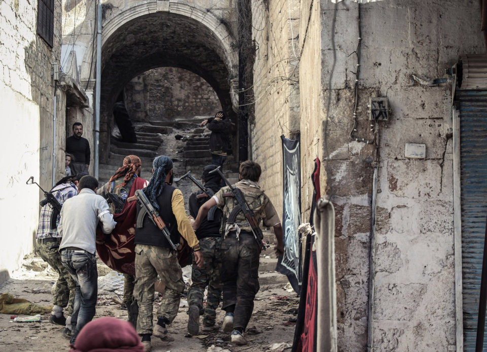 Photo -   In this Tuesday, Oct. 30, 2012 photo, a group of Free Syrian Army fighters carry a wounded comrade to cover in the town of Harem, Syria. Despite two weeks of attacking a Roman-era citadel in which pro-Assad militia are dug in, the rebels failed to secure the town. (AP Photo/Mustafa Karali)