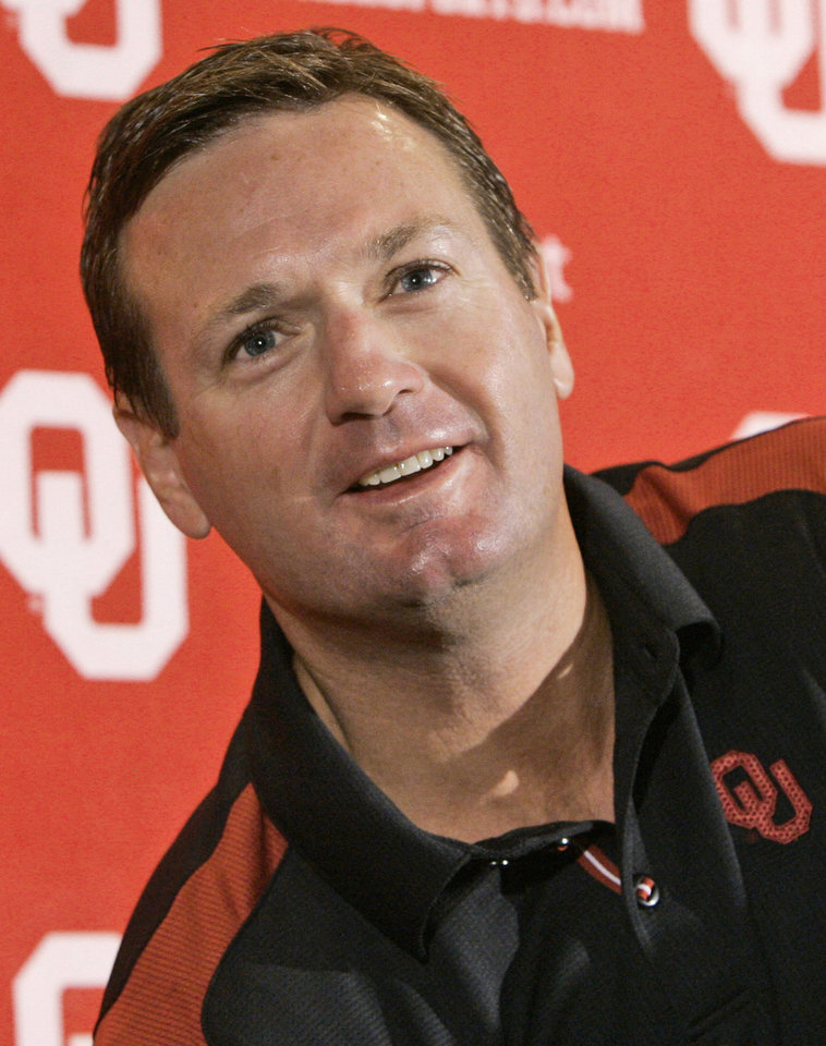Photo - **FILE**  OU: In this Oct. 7, 2008, file photo, University of Oklahoma college football head coach Bob Stoops smiles as he answers a question during a news conference in Norman, Okla. A clause in Stoops' contract provided for the 48-year-old coach to receive a so-called