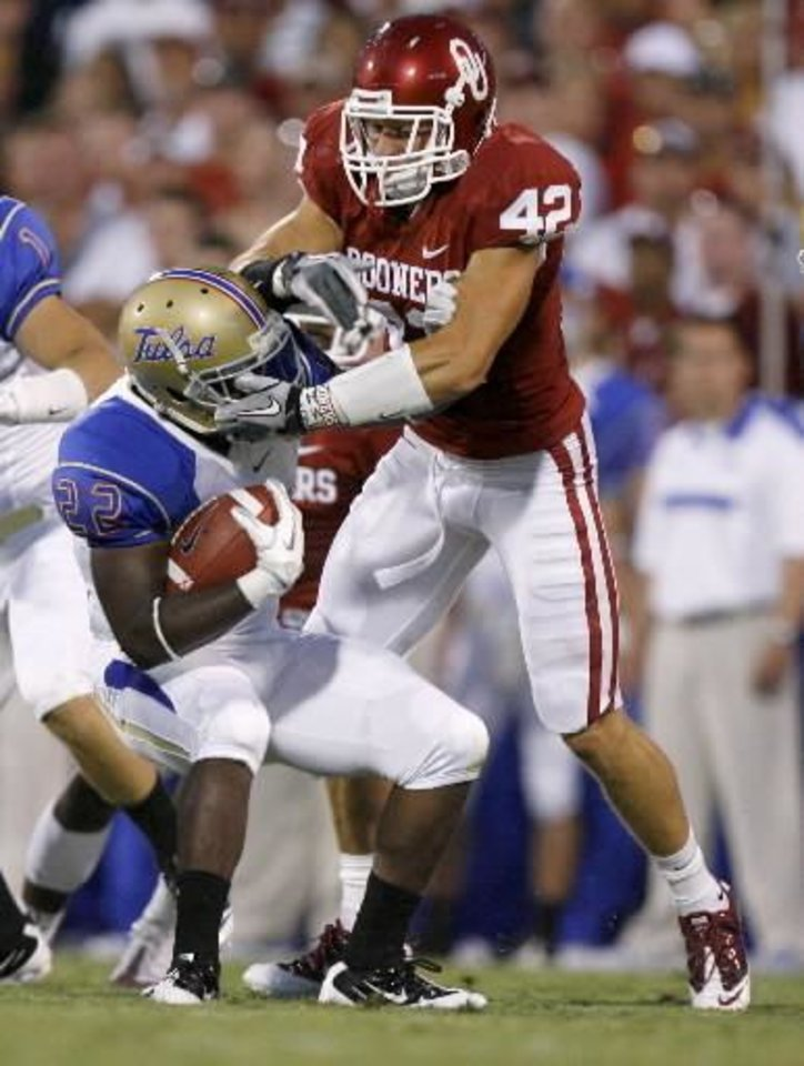 Photo - Oklahoma's Jesse Paulsen (42) brings down Tulsa's Trey Watts (22) during the college football game between the University of Oklahoma Sooners ( OU) and the Tulsa University Hurricanes (TU) at the Gaylord Family-Memorial Stadium on Saturday, Sept. 3, 2011, in Norman, Okla. Photo by Bryan Terry, The Oklahoman ORG XMIT: KOD