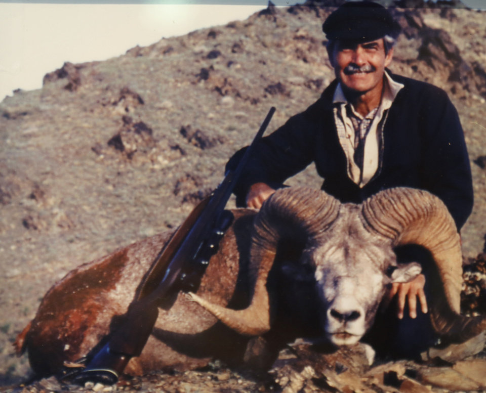 Photo - Bill Lockard's 1983 photo with a Gobi argali he shot in the Gobi desert of Mongolia hangs in his trophy room at his home in Oklahoma City, Wednesday July 31, 2013. Photo By Steve Gooch, The Oklahoman