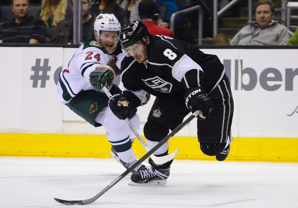 Photo - Minnesota Wild left wing Matt Cooke (24) reaches in as Los Angeles Kings defenseman Drew Doughty (8) keeps possession during the second period of an NHL hockey game, Monday, March 31, 2014, in Los Angeles. (AP Photo/Gus Ruelas)