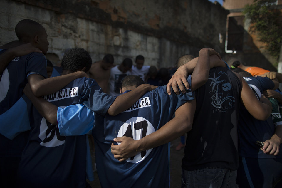 Photo - In this May 3, 2014 photo, Escada Azul players pray after their amateur soccer match in the Mangueira shantytown of Rio de Janeiro, Brazil. Brazil is a five-time champion of the World Cup, and will host this year's international soccer tournament starting June. 12. (AP Photo/Leo Correa)