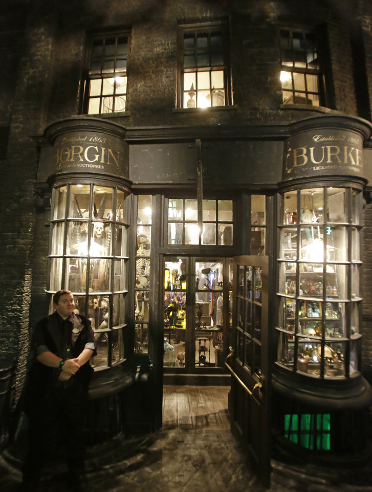 Photo - A man stands outside the entrance to Borgin and Burkes store in Knockturn Alley during a preview of Diagon Alley at the Wizarding World of Harry Potter at Universal Orlando, Thursday, June 19, 2014, in Orlando, Fla. (AP Photo/John Raoux)