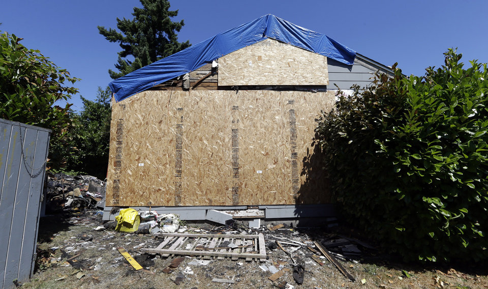 Photo - Debris from a fire remains in the yard next to the now boarded-up house where the night before a man used a can of spray paint and a lighter as a makeshift blowtorch to kill a spider, Wednesday, July 16, 2014, in Seattle. The makeshift blowtorch started a blaze that caused $60,000 worth of damage, Seattle fire officials said Wednesday. The man and his mother got out of the house, and no injuries were reported. (AP Photo/Elaine Thompson)