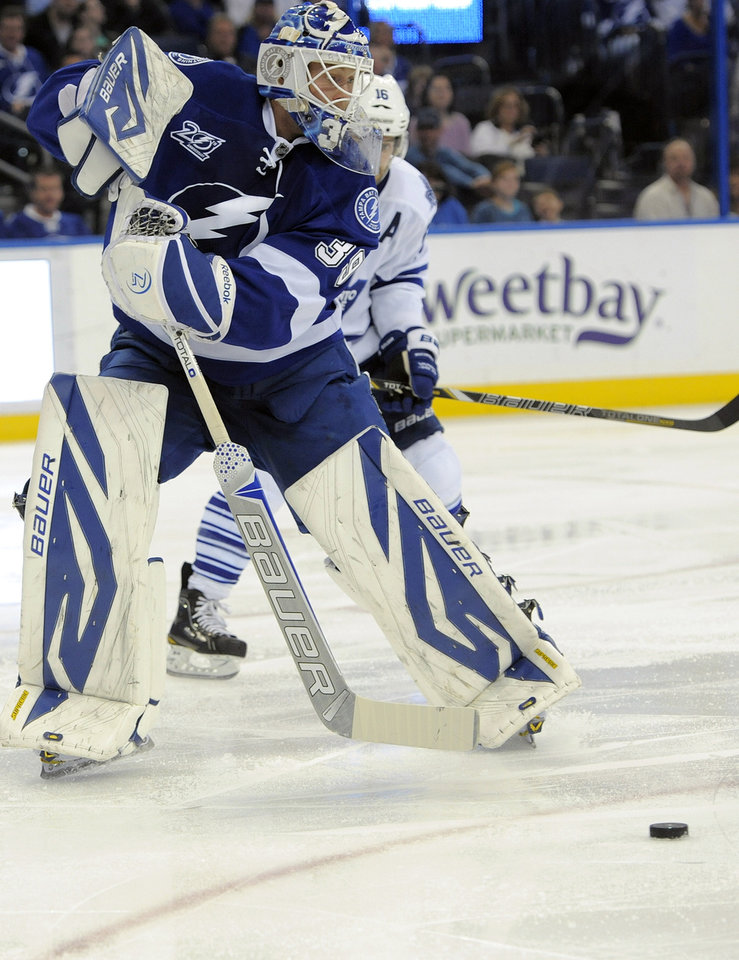 Tampa Bay Lightning goalie Anders Lindback (39) defends the puck from Toronto Maple Leafs left wing Clarke MacArthur (16) during the third period of an NHL hockey game Tuesday, Feb. 19, 2013, in Tampa, Fla. (AP Photo/Brian Blanco)