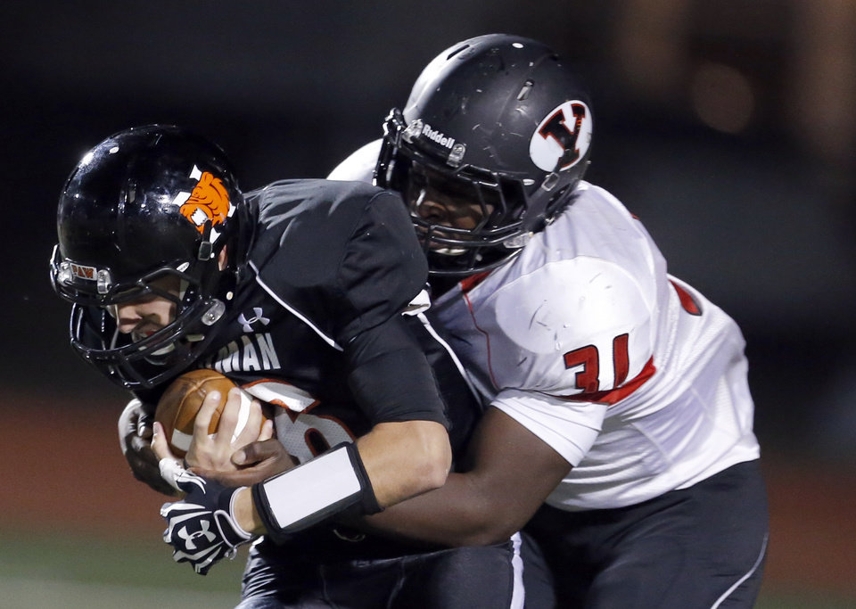Photo - Norman's Zach Long is tackled by Yukon's Andre Dowuona Hammond during the high school football game between Norman and Yukon at Norman High School in Norman, Okla., Thursday, Nov. 8, 2012. Photo by Sarah Phipps, The Oklahoman