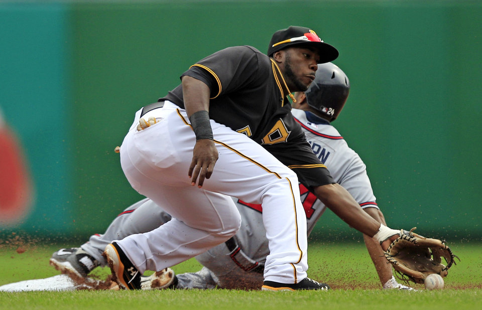 Pittsburgh Pirates shortstop Josh Harrison (5) can't handle the throw from catcher Rod Barajas as Atlanta Braves' Michael Bourn (24) steals second during the first inning of a baseball game in Pittsburgh, Wednesday, Oct. 3, 2012. (AP Photo/Gene J. Puskar)