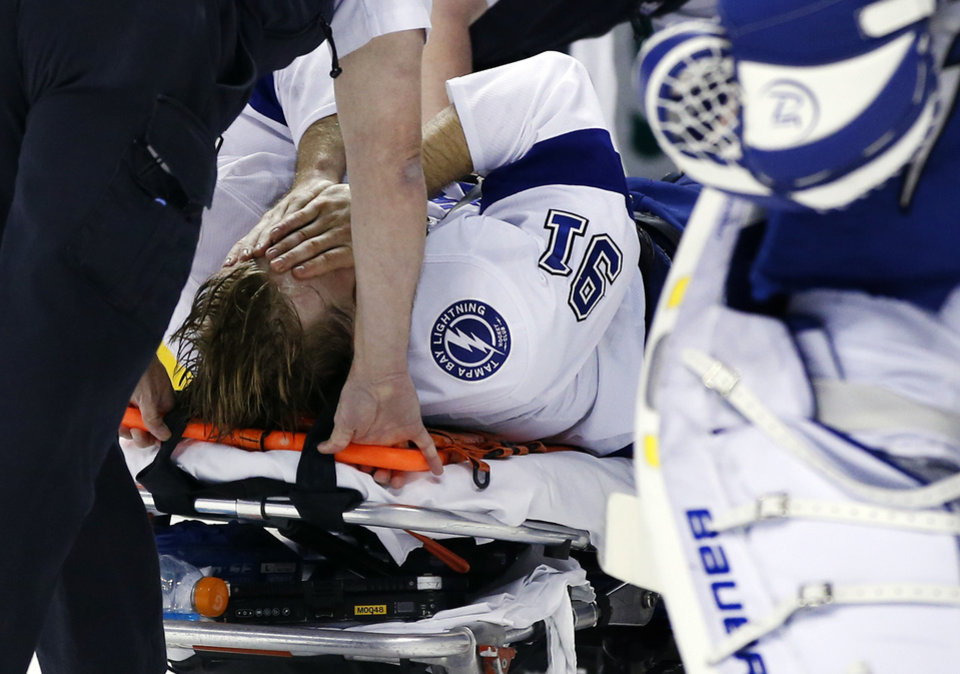Photo - Tampa Bay Lightning center Steven Stamkos is taken off the ice on a stretcher after banging into the goalpost during the second period of an NHL hockey game against the Boston Bruins in Boston Monday, Nov. 11, 2013. (AP Photo/Elise Amendola)