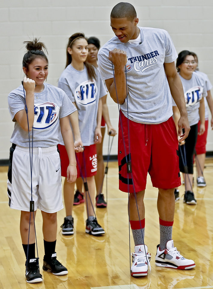 Russell Westbrook works on some curl exercises with Aidee Perez during a visit by the Oklahoma City Thunder to students at U.S. Grant High School to promote physical fitness on Monday, Jan. 28, 2013, in Oklahoma City, Okla. Photo by Chris Landsberger, The Oklahoman